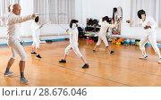 Купить «Coaches demonstrating to young athletes attack movements with rapier during fencing workout», фото № 28676046, снято 30 мая 2018 г. (c) Яков Филимонов / Фотобанк Лори