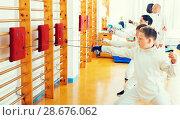 Купить «Group practicing fencing techniques in gym», фото № 28676062, снято 30 мая 2018 г. (c) Яков Филимонов / Фотобанк Лори