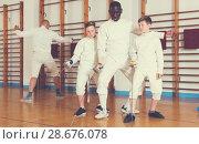 Купить «Coach demonstrating fencing movements to kids», фото № 28676078, снято 30 мая 2018 г. (c) Яков Филимонов / Фотобанк Лори