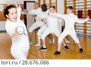 Купить «Young woman fencer practicing effective fencing techniques in training room», фото № 28676086, снято 30 мая 2018 г. (c) Яков Филимонов / Фотобанк Лори