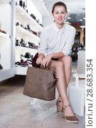 Купить «Young woman is posing with new handbag and fashion footwear», фото № 28683354, снято 13 декабря 2017 г. (c) Яков Филимонов / Фотобанк Лори