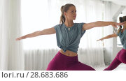 Купить «woman doing yoga warrior pose at studio», видеоролик № 28683686, снято 28 июня 2018 г. (c) Syda Productions / Фотобанк Лори