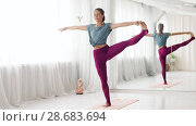 Купить «woman doing yoga hand-to-big-toe pose at studio», видеоролик № 28683694, снято 28 июня 2018 г. (c) Syda Productions / Фотобанк Лори