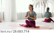 Купить «woman meditating at yoga studio», видеоролик № 28683714, снято 28 июня 2018 г. (c) Syda Productions / Фотобанк Лори