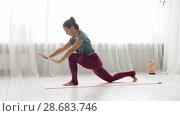 Купить «woman making high lunge exercise at yoga studio», видеоролик № 28683746, снято 28 июня 2018 г. (c) Syda Productions / Фотобанк Лори