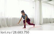Купить «woman making high lunge exercise at yoga studio», видеоролик № 28683750, снято 28 июня 2018 г. (c) Syda Productions / Фотобанк Лори