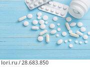 Купить «white pills on blue wooden background», фото № 28683850, снято 3 июля 2018 г. (c) Майя Крученкова / Фотобанк Лори