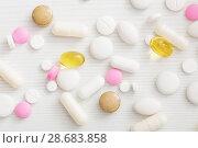 Купить «pills on white wooden table», фото № 28683858, снято 3 июля 2018 г. (c) Майя Крученкова / Фотобанк Лори