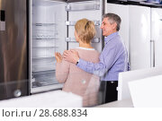 Купить «interested mature married couple in shop of household appliances are choosing home modern refrigerator», фото № 28688834, снято 18 июля 2018 г. (c) Яков Филимонов / Фотобанк Лори
