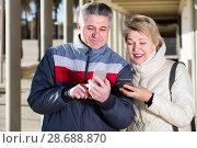 Купить «mature husband and wife go nearby with each other and speak by mobile phone», фото № 28688870, снято 20 августа 2019 г. (c) Яков Филимонов / Фотобанк Лори