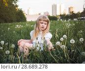 Купить «Portrait of a child in the grass among the flowers. The concept of urban ecology», фото № 28689278, снято 17 июля 2018 г. (c) Ирина Козорог / Фотобанк Лори