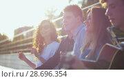 Купить «Attractive young friends hipsters singing songs with a guitar at summer sunset outdoors», видеоролик № 28696354, снято 17 июля 2018 г. (c) Константин Шишкин / Фотобанк Лори