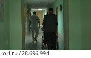 Купить «Muslim man in skullcap carries a disabled person in a wheelchair along the corridor», видеоролик № 28696994, снято 17 июля 2018 г. (c) Константин Шишкин / Фотобанк Лори