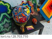 Купить «Москва. Сувенирный инкрустированный футбольный мяч с портретами футболистов. Изделие индейцев племени Уичоли, выполнено в технике бисерной мозаики и вышивки. Национальный дом для мексиканских болельщиков в Гостином дворе», фото № 28703710, снято 29 июня 2018 г. (c) Алёшина Оксана / Фотобанк Лори