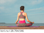 Купить «Sporty young girl in the morning on seashore, practicing yoga. Woman do gymnastics outdoor. Health and Yoga Concept», фото № 28704546, снято 23 июня 2018 г. (c) Сергей Тимофеев / Фотобанк Лори