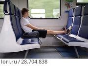 Купить «Молодой человек сидит в вагоне пригородной электрички, положив ноги в обуви на соседнее кресло», эксклюзивное фото № 28704838, снято 30 июня 2018 г. (c) Елена Коромыслова / Фотобанк Лори