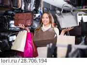 Купить «Young active woman buying leather purse in shop», фото № 28706194, снято 24 сентября 2018 г. (c) Яков Филимонов / Фотобанк Лори