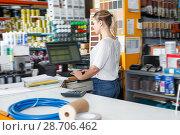 Купить «Portrait of glad woman seller at cash desk», фото № 28706462, снято 17 мая 2018 г. (c) Яков Филимонов / Фотобанк Лори