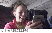 Купить «Cheerful teenage girl plays a game on smartphone in the cabin of the plane while traveling stock footage video», видеоролик № 28722970, снято 27 июня 2018 г. (c) Юлия Машкова / Фотобанк Лори