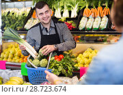 Купить «Young seller helping customer to buy vegetables», фото № 28723674, снято 18 марта 2017 г. (c) Яков Филимонов / Фотобанк Лори