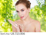 Купить «happy young woman with moisturizing cream on hand», фото № 28723806, снято 14 апреля 2016 г. (c) Syda Productions / Фотобанк Лори
