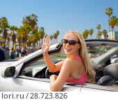 Купить «happy young woman in convertible car waving hand», фото № 28723826, снято 17 августа 2017 г. (c) Syda Productions / Фотобанк Лори