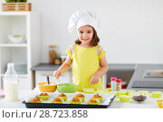 Купить «little girl in chefs toque baking muffins at home», фото № 28723858, снято 20 октября 2017 г. (c) Syda Productions / Фотобанк Лори