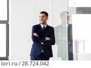 Купить «smiling businessman at office glass wall», фото № 28724042, снято 8 июня 2018 г. (c) Syda Productions / Фотобанк Лори