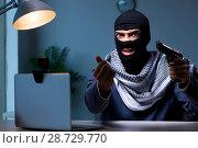 Купить «Terrorist burglar with gun working at computer», фото № 28729770, снято 8 сентября 2017 г. (c) Elnur / Фотобанк Лори