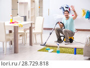 Купить «Young man husband doing vacuuming at home», фото № 28729818, снято 1 мая 2018 г. (c) Elnur / Фотобанк Лори