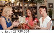 Купить «women giving present to friend at wine bar», видеоролик № 28730634, снято 4 июля 2018 г. (c) Syda Productions / Фотобанк Лори