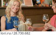 Купить «women giving present to friend at wine bar», видеоролик № 28730682, снято 4 июля 2018 г. (c) Syda Productions / Фотобанк Лори