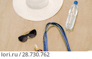 Купить «beach bag, sunscreen, sunglasses and hat on sand», видеоролик № 28730762, снято 5 июля 2018 г. (c) Syda Productions / Фотобанк Лори