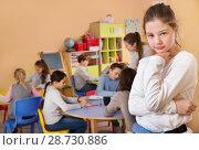 Купить «Upset girl in schoolroom on background with pupils», фото № 28730886, снято 28 января 2018 г. (c) Яков Филимонов / Фотобанк Лори