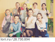 Купить «Pupils with teacher giving thumbs up in schoolroom», фото № 28730894, снято 28 января 2018 г. (c) Яков Филимонов / Фотобанк Лори