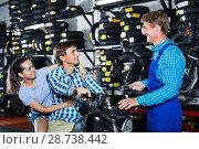 Купить «Portrait man and woman sitting on motorbike and chatting with mechanic man», фото № 28738442, снято 15 июля 2018 г. (c) Яков Филимонов / Фотобанк Лори