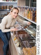 Купить «Positive female customer selecting various nuts», фото № 28738466, снято 15 ноября 2018 г. (c) Яков Филимонов / Фотобанк Лори