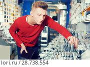 Купить «Serious young guy looking new CD and DVD in shop», фото № 28738554, снято 15 февраля 2018 г. (c) Яков Филимонов / Фотобанк Лори
