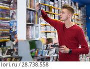 Купить «Joyful man browsing contents on DVD cover», фото № 28738558, снято 15 февраля 2018 г. (c) Яков Филимонов / Фотобанк Лори