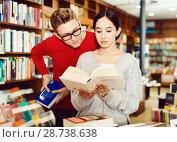 Купить «Girl reading book in bookstore while guy looking at her book over her shoulder», фото № 28738638, снято 18 января 2018 г. (c) Яков Филимонов / Фотобанк Лори
