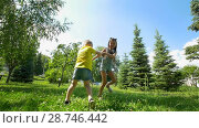 Купить «Cute little boy runs away from his happy sister through the spruce trees at sunny day», видеоролик № 28746442, снято 21 июля 2018 г. (c) Константин Шишкин / Фотобанк Лори
