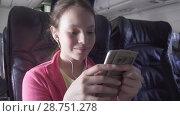 Купить «Cheerful teenage girl plays a game on smartphone in the cabin of the plane while traveling stock footage video», видеоролик № 28751278, снято 27 июня 2018 г. (c) Юлия Машкова / Фотобанк Лори