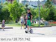 Купить «Tyumen, Russia, on July 15, 2018: the teenage boy rides a giroskuter in the summer on the square..», фото № 28751742, снято 15 июля 2018 г. (c) Землянникова Вероника / Фотобанк Лори