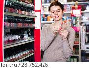 Купить «Smiling woman customer browsing rows of lipstick», фото № 28752426, снято 21 февраля 2017 г. (c) Яков Филимонов / Фотобанк Лори