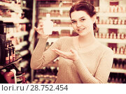 Купить «satisfied female customer deciding on make-up items in cosmetics shop», фото № 28752454, снято 21 февраля 2017 г. (c) Яков Филимонов / Фотобанк Лори