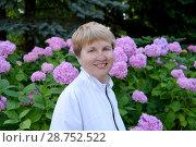 Купить «Портрет зрелой женщины на фоне цветущей гортензии», фото № 28752522, снято 8 июля 2018 г. (c) Ирина Борсученко / Фотобанк Лори