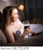 Купить «Young woman is sitting with white wine and watching TV», фото № 28772670, снято 19 апреля 2018 г. (c) Яков Филимонов / Фотобанк Лори