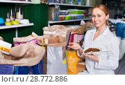 Купить «Girl seller showing different types of food for pets», фото № 28772886, снято 6 декабря 2019 г. (c) Яков Филимонов / Фотобанк Лори