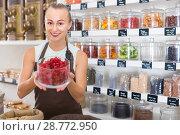 Купить «Young woman is offering dried flowers of Hibiscus in container», фото № 28772950, снято 4 сентября 2017 г. (c) Яков Филимонов / Фотобанк Лори