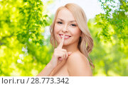 Купить «woman with finger on lips over natural background», фото № 28773342, снято 7 января 2014 г. (c) Syda Productions / Фотобанк Лори